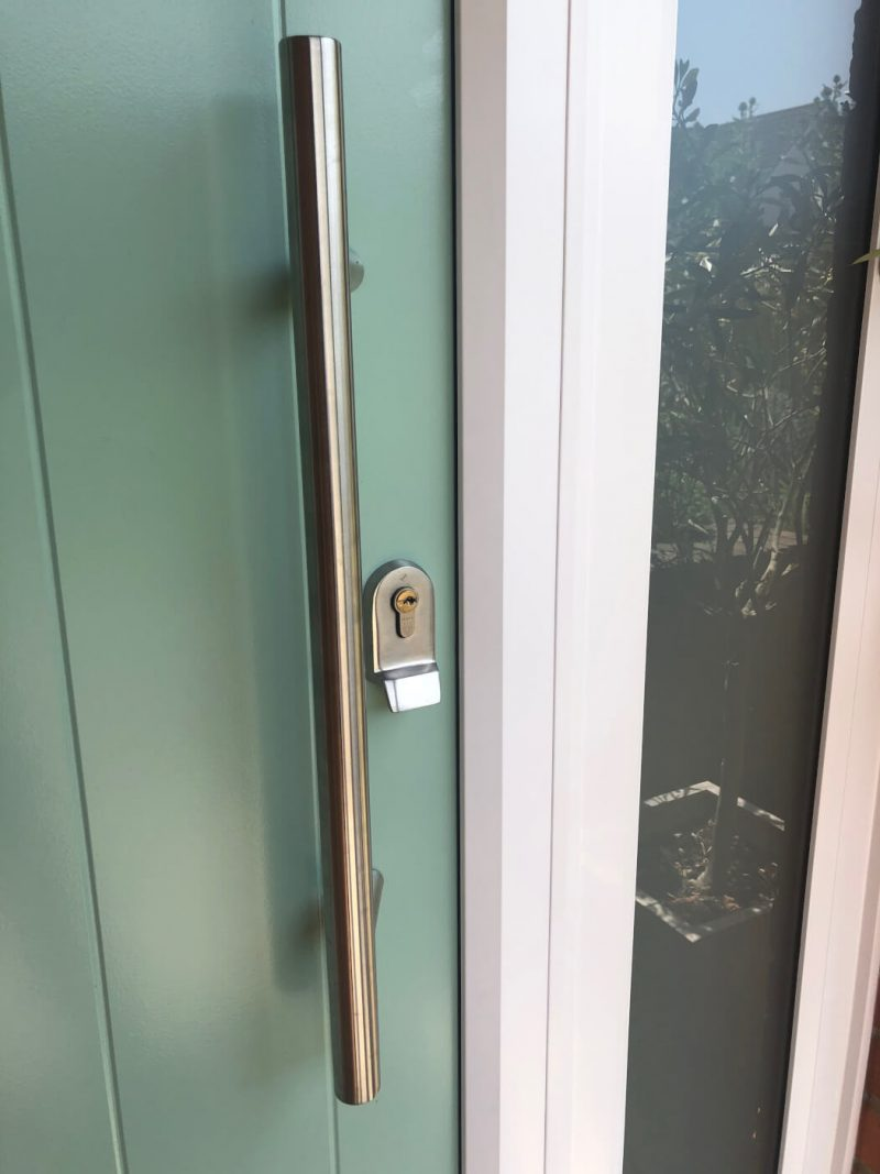Close up of composite door bar handle and locking cylinder